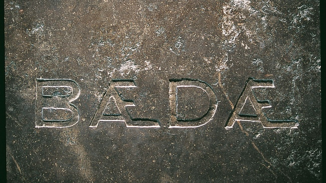 Inscription in stone on Bede's tomb at Durham Cathedral